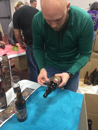 People applying bottle labels by hand.