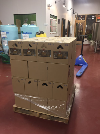 Full pallet of boxed bottles of beer.